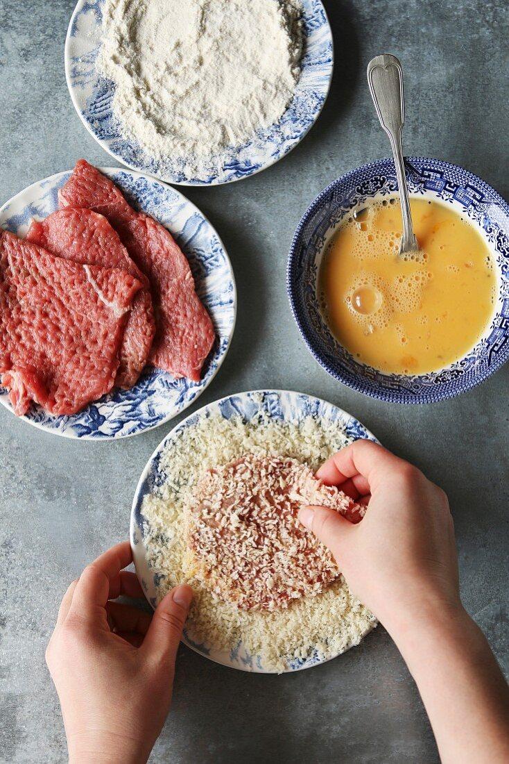 Preparing schnitzel by hands coating beef in breadcrumbs
