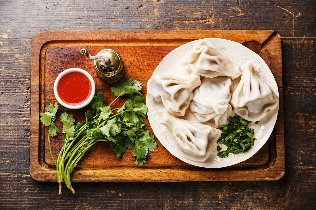 Georgian dumplings Khinkali with meat and tomato spicy sauce satsebeli on wooden background