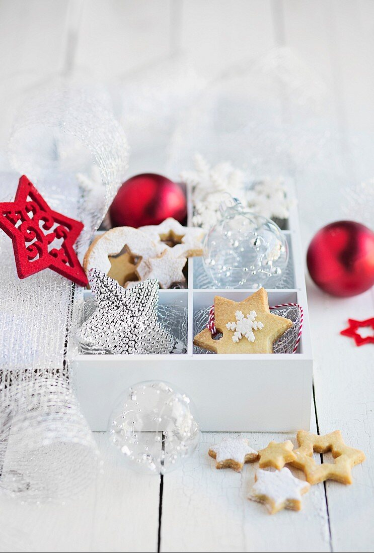 Box with christmas biscuits and decorations on white table