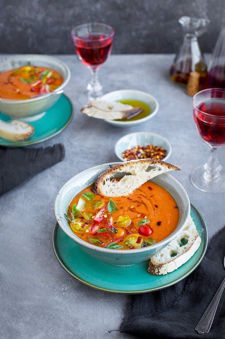 Roasted Tomato Herb Soup topped with cherry tomatoes and basil, served in ceramic bowls served with rose wine, bread and olive oil