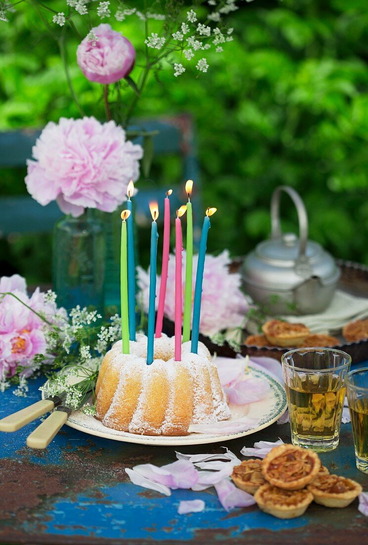 A garden table with peonies, a 'Gugelhupf' ring cake with candles and springtime herb tea