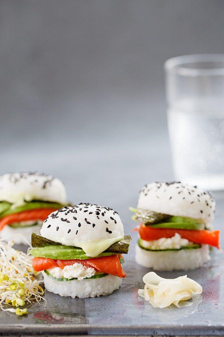Three sushi burgers with smoked salmon, cucumber, fresh cheese, wasabi, nori and avocado