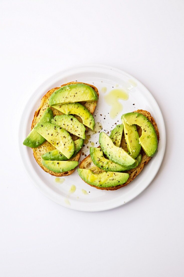 Two slices of bread with olive oil and fresh avocado with black peeper on a white plate