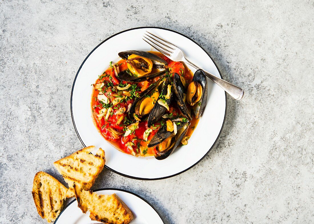 Steamed New England mussels in stewed tomatoes served with a side of grilled sour dough bread