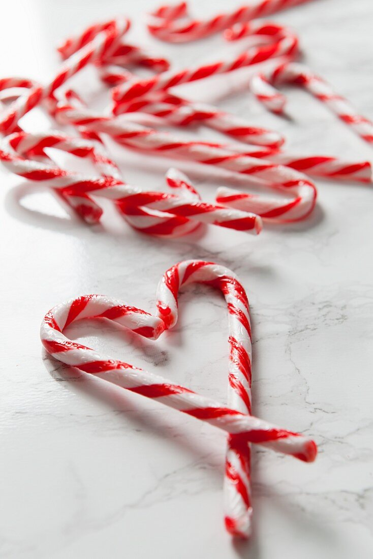 White marble surface covered in candy canes and two canes in the foreground forming a heart shape