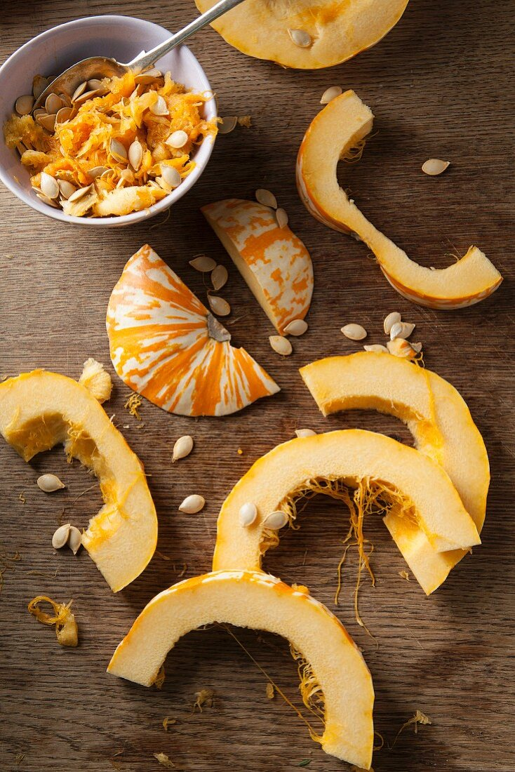 Sliced munchkin pumpkins and pumpkin seeds on a rustic wooden surface