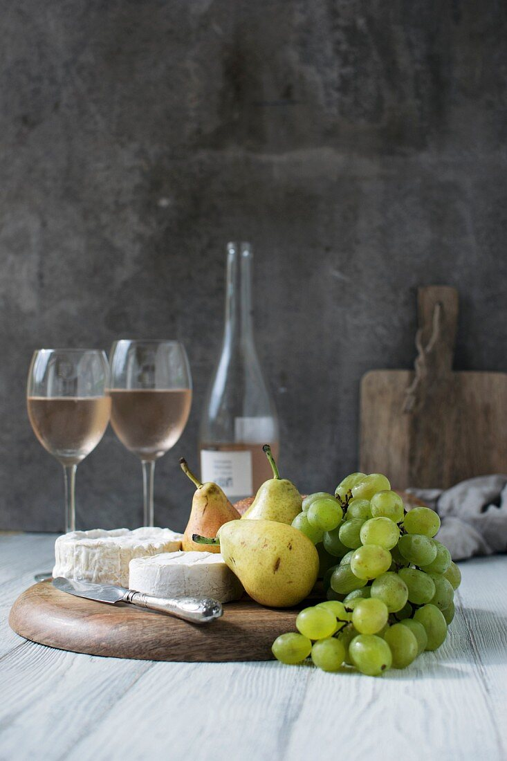 An arrangement of cheese, pears, grapes and rosé wine