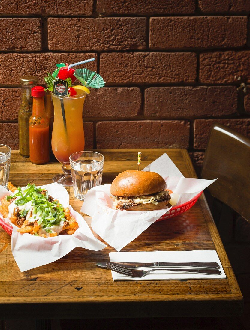 A beef brisket sandwich with chili cheese fries and a cocktail in a restaurant (Melbourne, Australia)