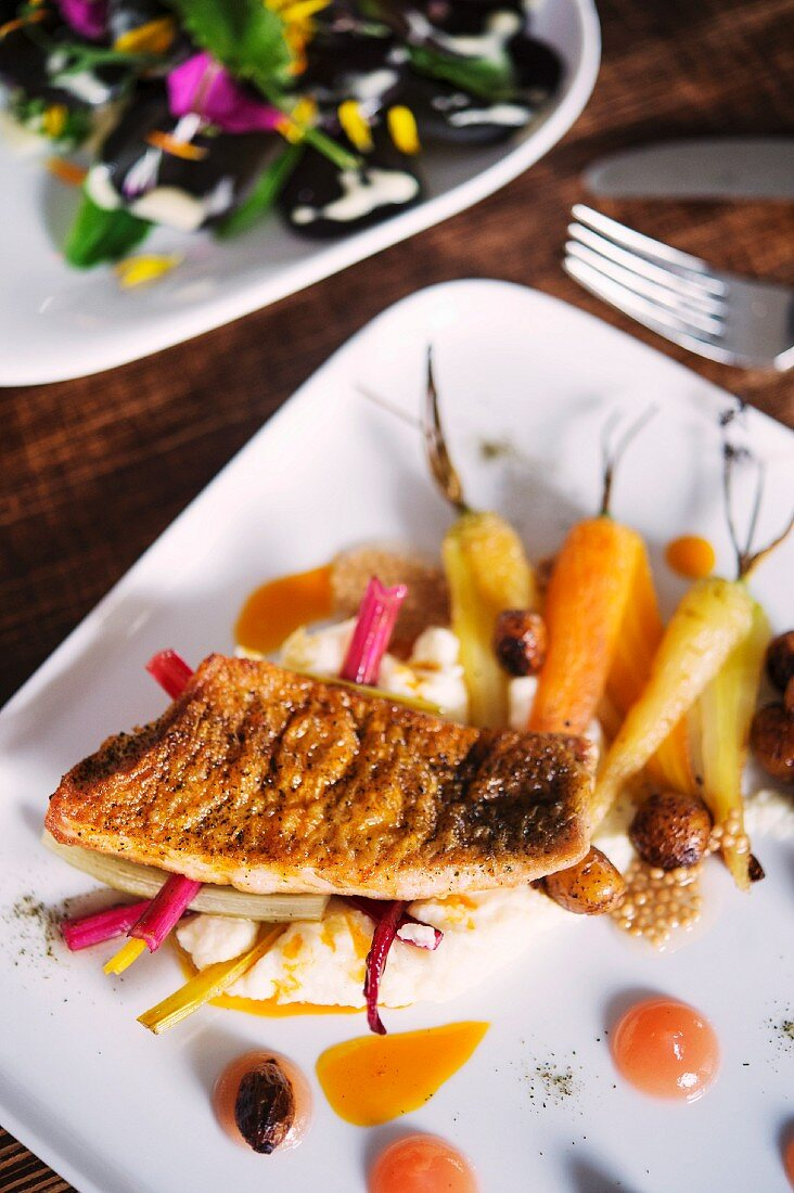 Perch on a bed of carrots and chard served at the 'Oberstübchen' restaurant next to the ECF Farm in Berlin, Germany