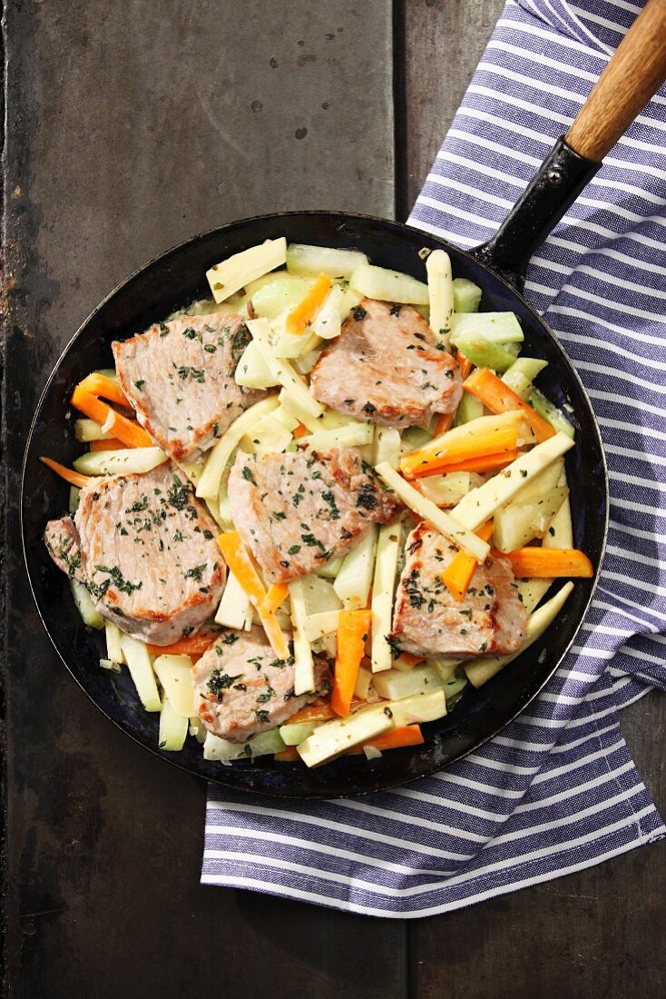 Schnitzel meat in a pan with root vegetables