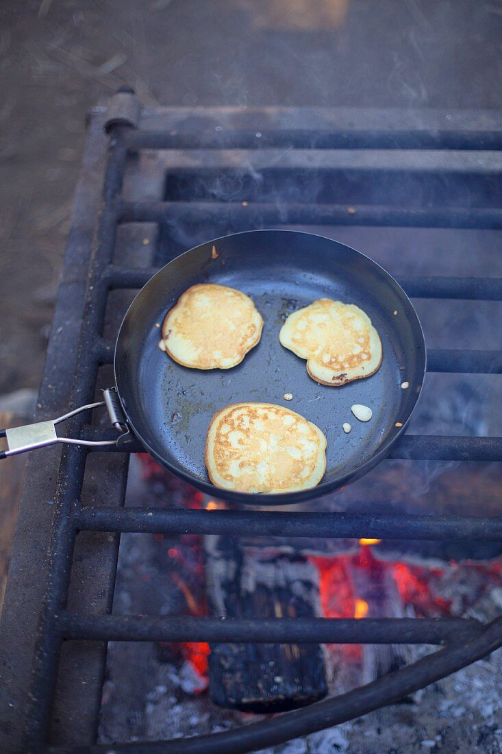 Pancakes in a pan on a fire grate