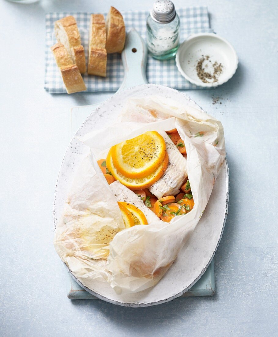 Redfish with orange slices and ginger carrots baked in parchment paper