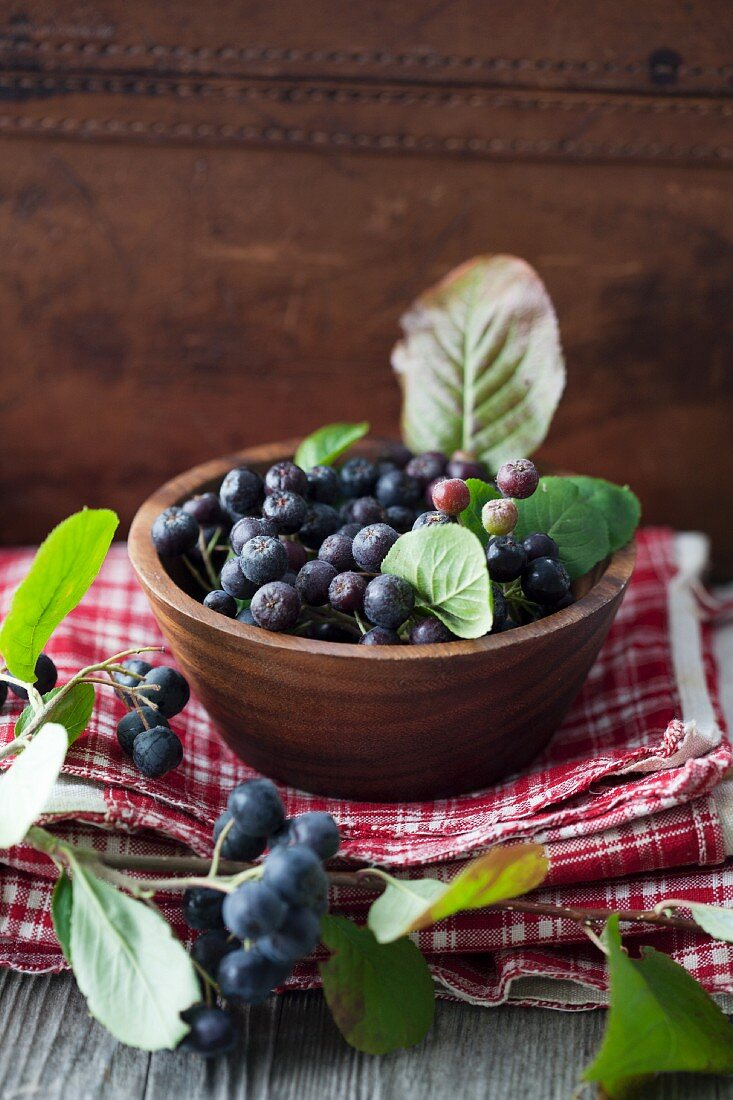 Aronia berries in a wooden bowl