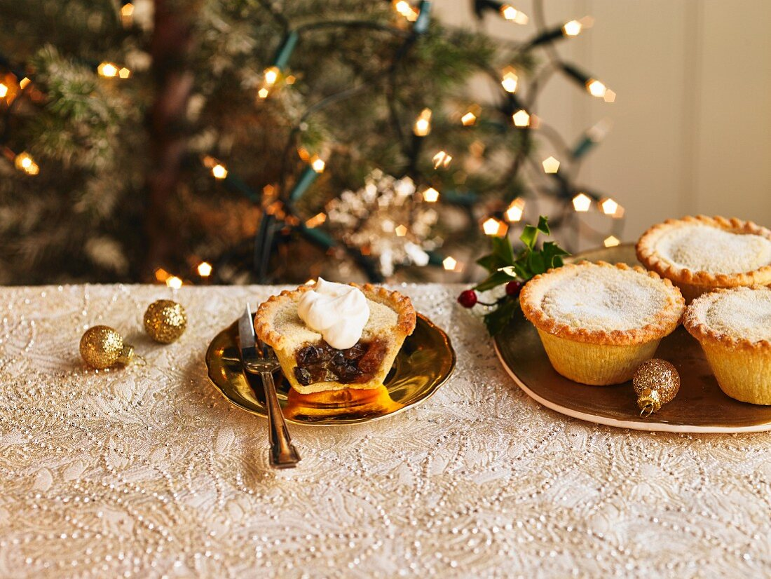 A plate of filled mince pies and one mince pie cut open with a dollop of cream