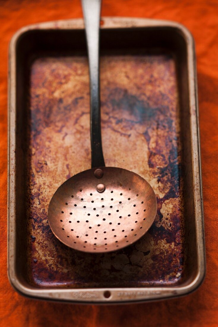 A burnt roasting tin with a strainer spoon
