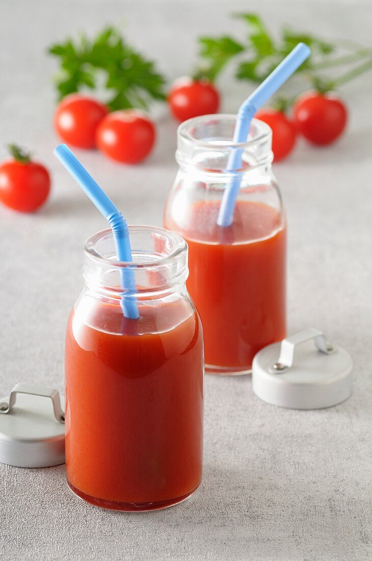 Two bottles of tomato juice with straws