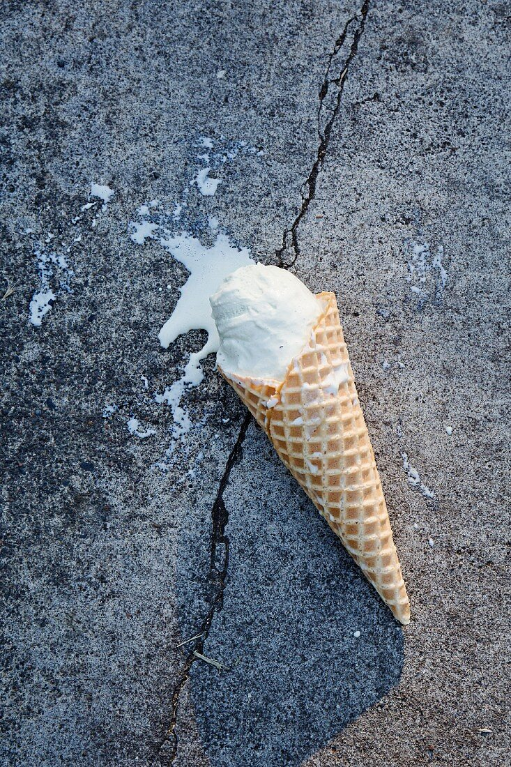 An ice cream cone on asphalt (top view)