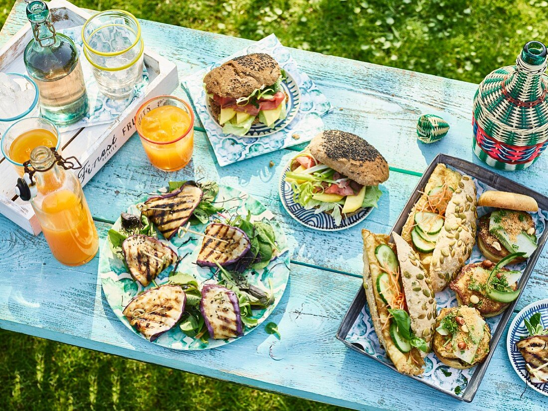 A table laid in a garden with sandwiches and drinks
