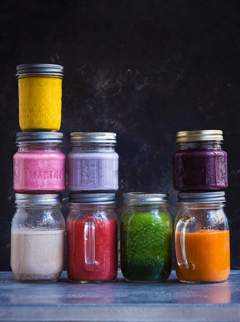 Assorted colourful smoothies in screw-top jars