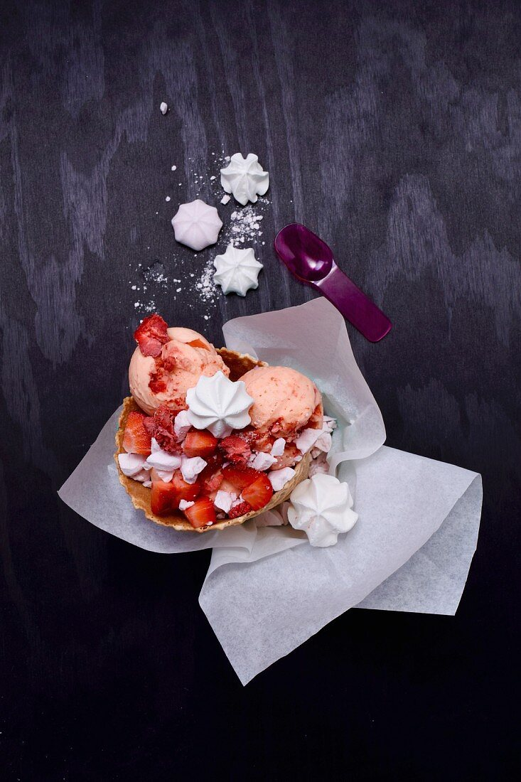 Peach and strawberry ice cream in waffles with fresh and freeze-dried strawberries and meringue