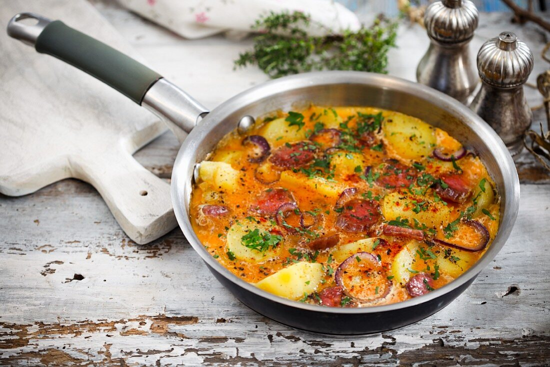 Omelette with potatoes and sausage in a pan