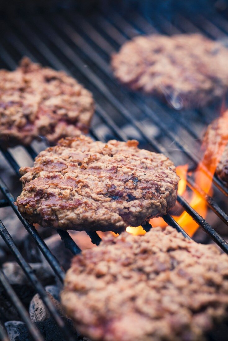 Beefburgers on a charcoal barbecue