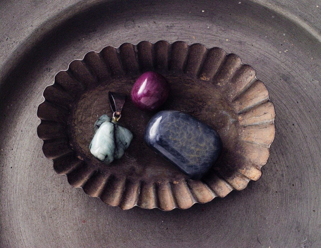 An emerald, a ruby and a sapphire in a vintage bowl