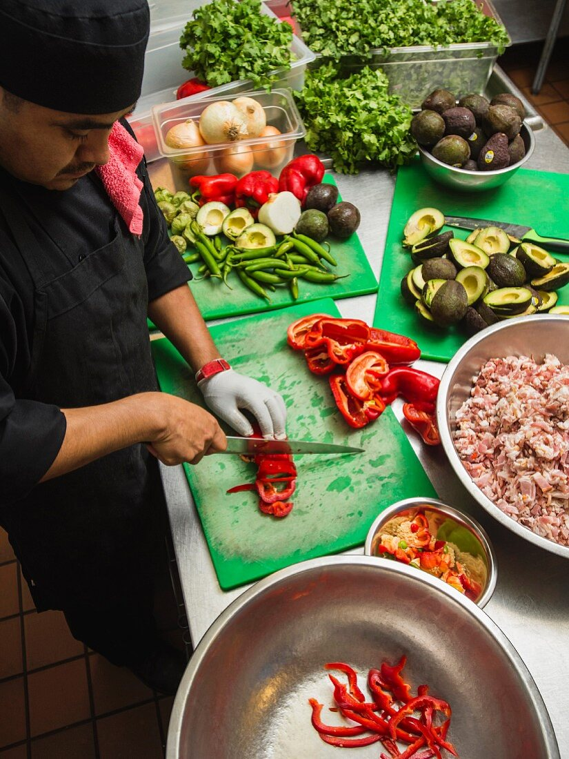 A Latin American cook chopping vegetables in a kitchen