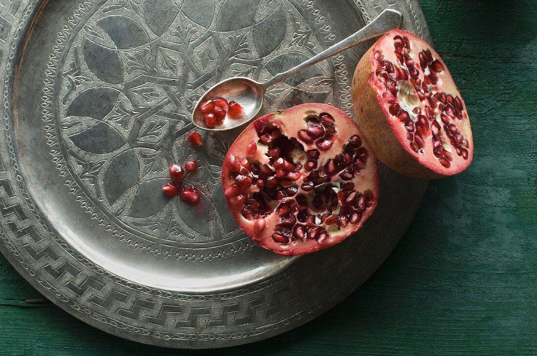 A halved pomegranate on a decorative metal plate