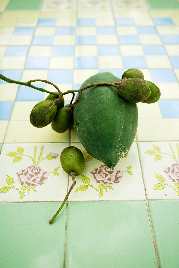 A fresh green papaya and hog plums