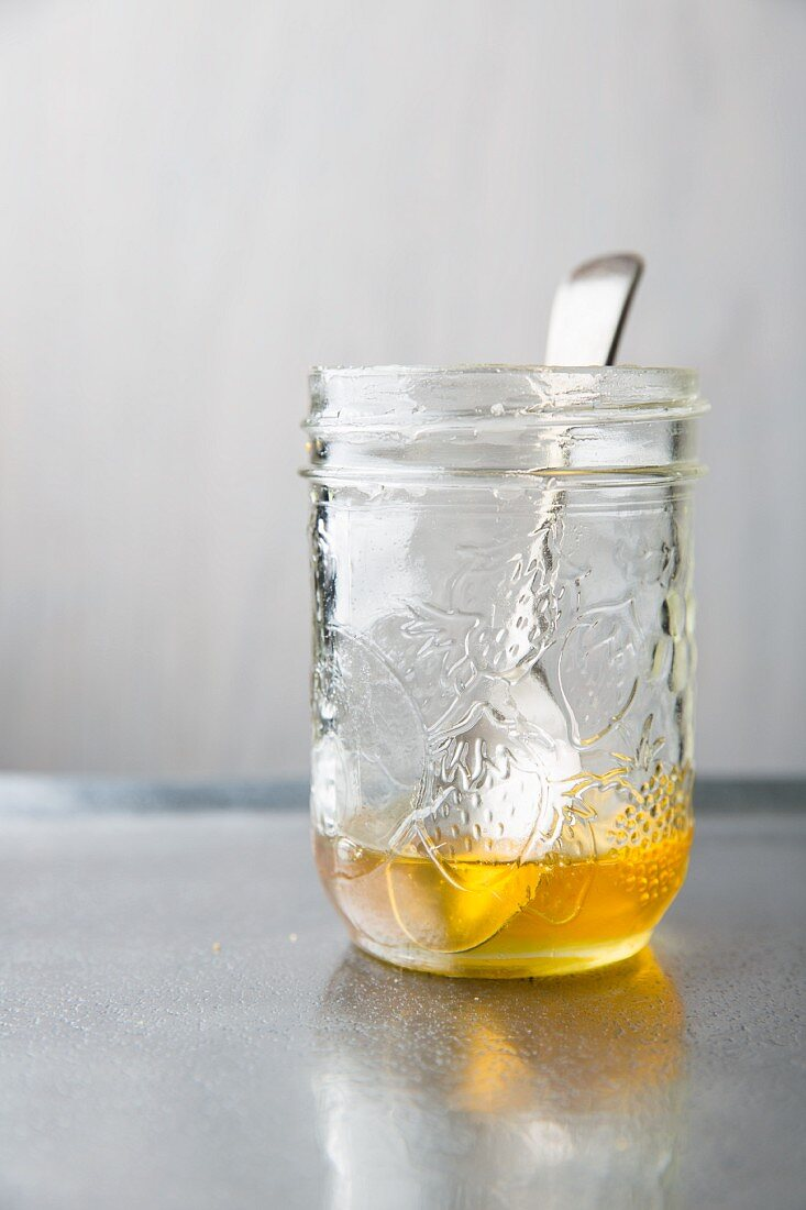 Honey in preserving jar with a spoon on a metal tray