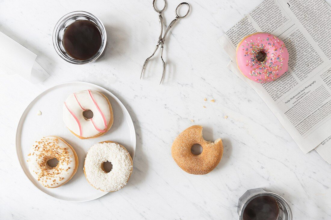Iced doughnuts and a cinnamon-sugar doughnut with a bite taken out on a marble table