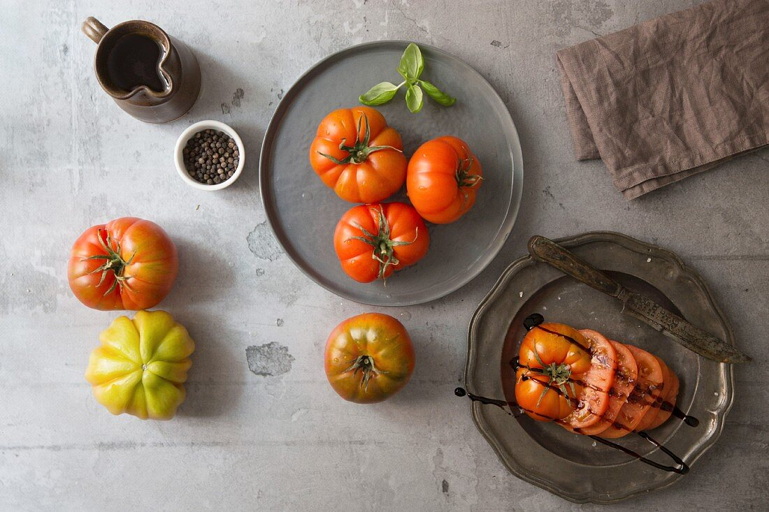 An arrangement of tomatoes with a sliced balsamic tomato