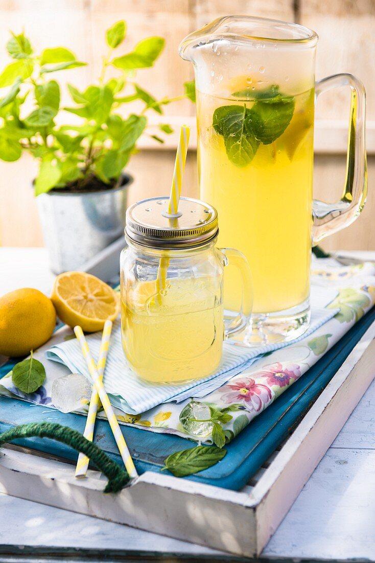 Homemade lemonade with fresh lemons on a tray