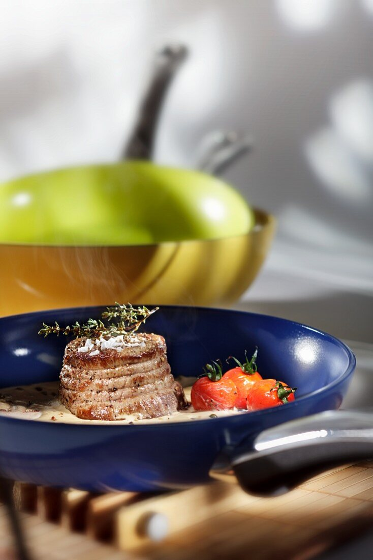 Tied and fried beef fillet with cherry tomatoes and thyme in a green pepper sauce