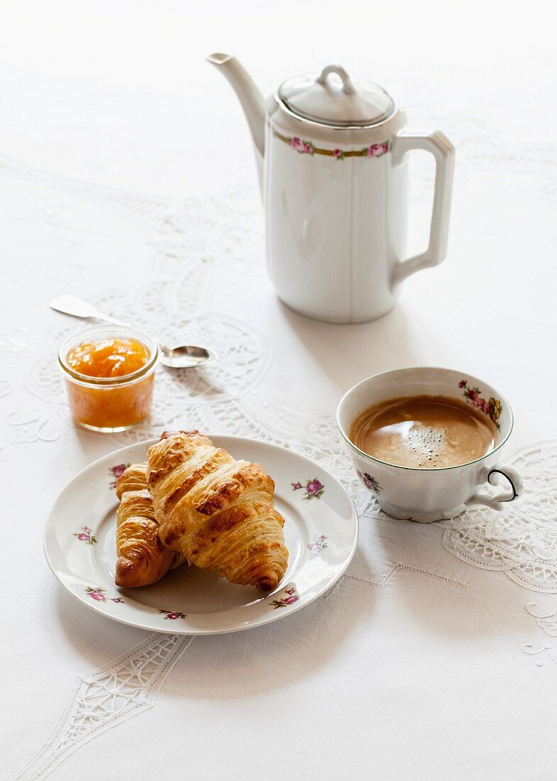 Croissants, a glass of apricot jam, a cup of coffee and a jug of coffee