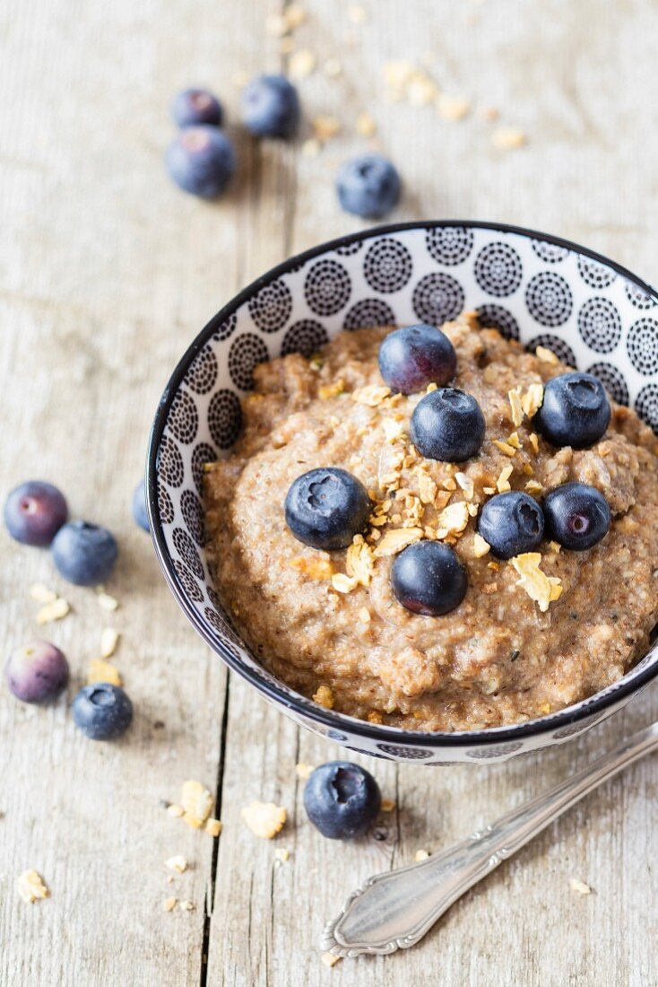 Gluten-free vegan tigernut porridge with hemp seeds, teff flakes and berries
