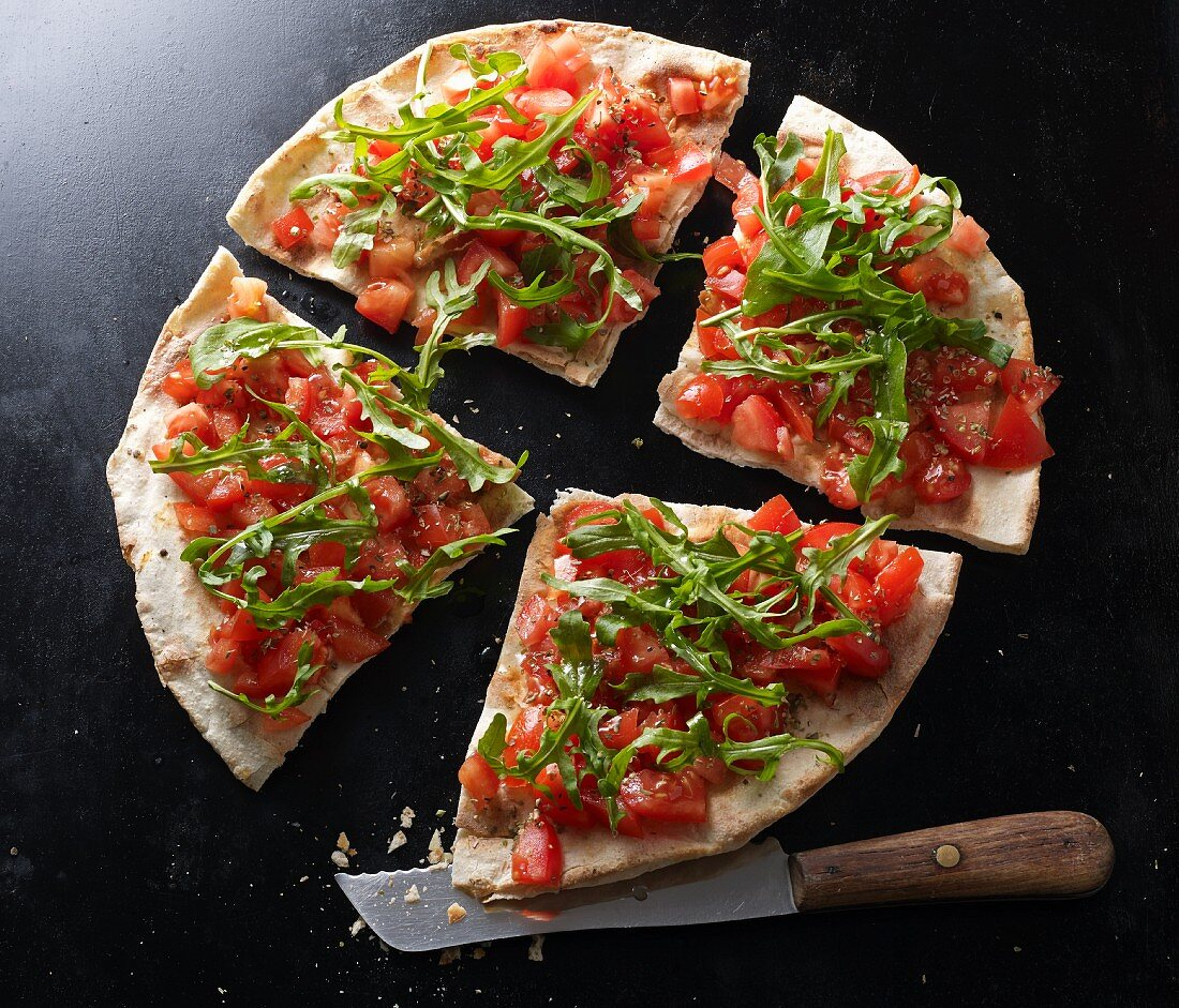 Bruschetta pizza with a knife on a black baking tray