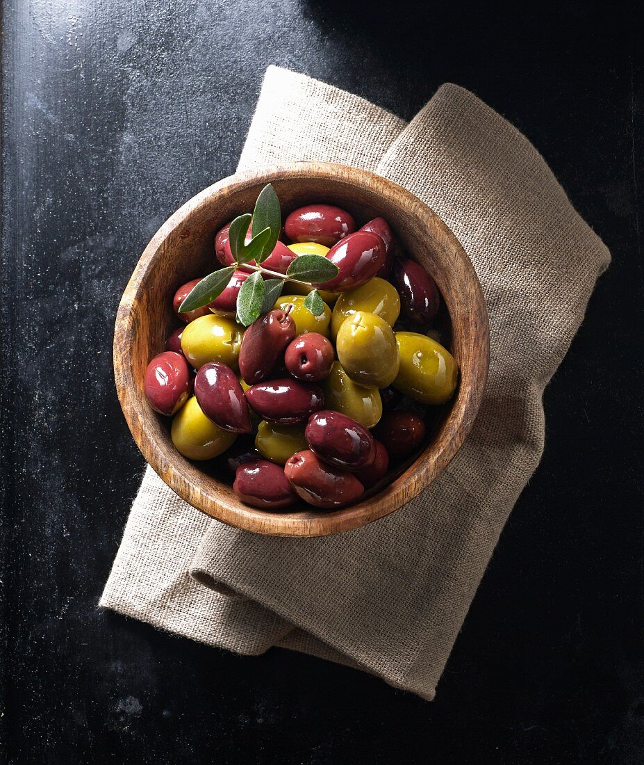 Kalamata olives and green olives in a wooden bowl on a linen napkin