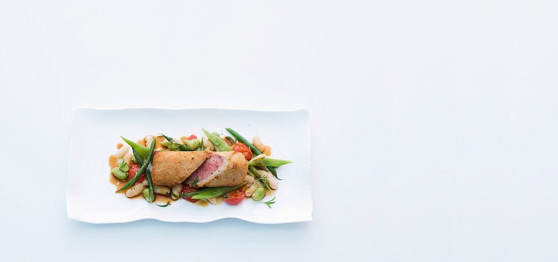Saddle of lamb wrapped in white bread on a bed of mixed beans