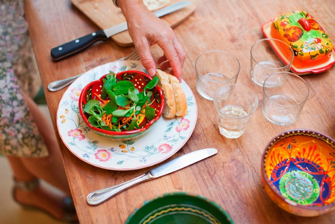 A country table laid with a bowl of salad, glasses and butter