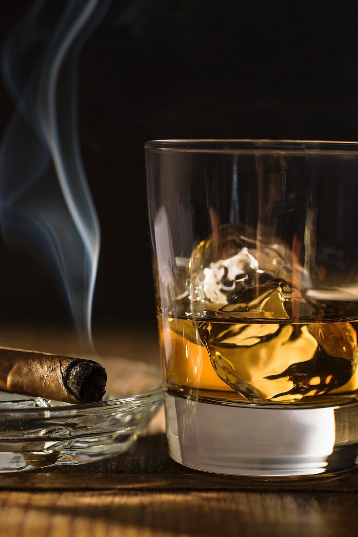 A smoking cigar next to a glass of whiskey