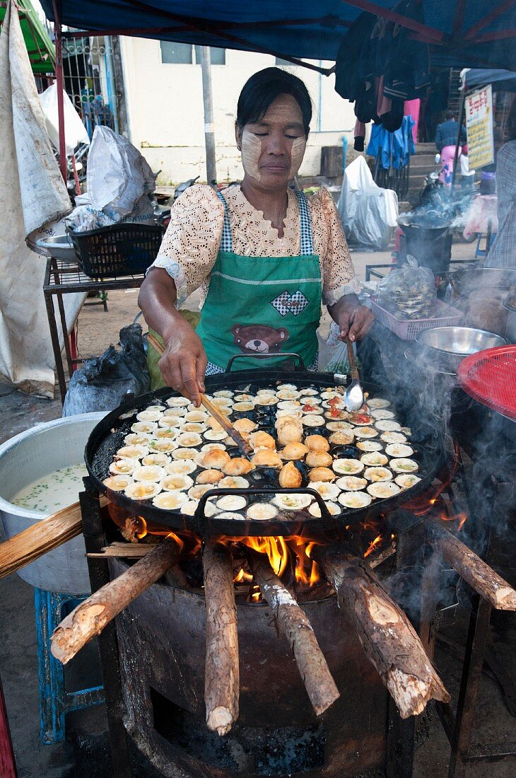 A woman making fritters in a street kitchen (Myanmar, Burma)