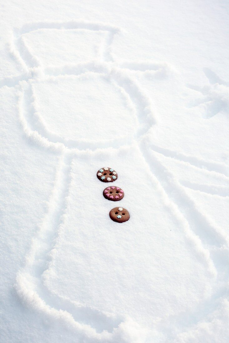 A snowman drawn in snow with gingerbread buttons