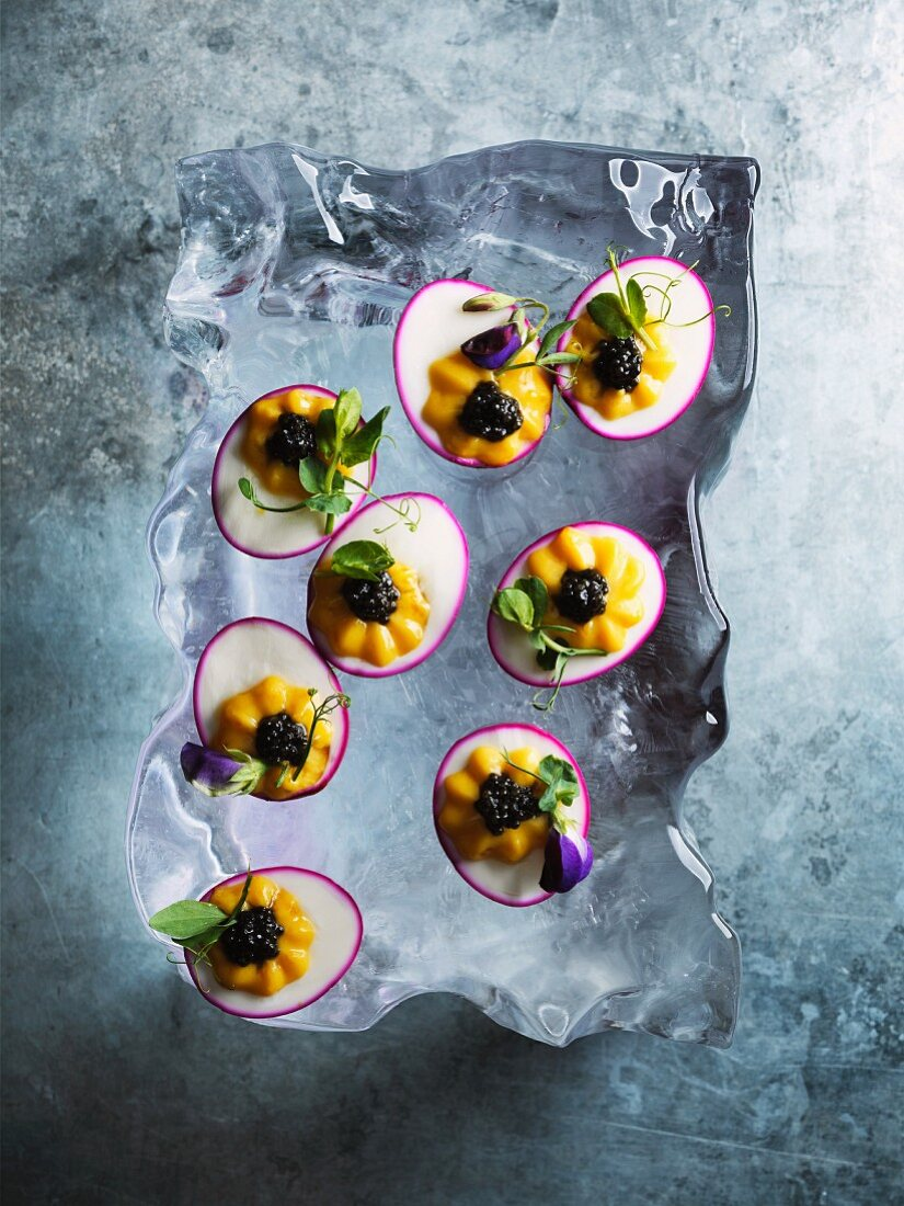 Filled eggs pickled in beetroot and topped with caviar