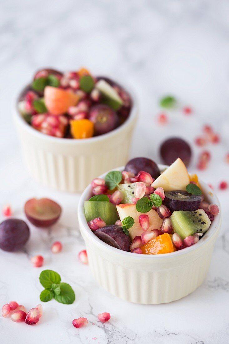 Fruit salad with grapes, kiwi, orange and pomegranate seeds