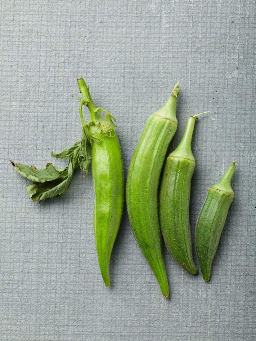 Four okra pods with leaves