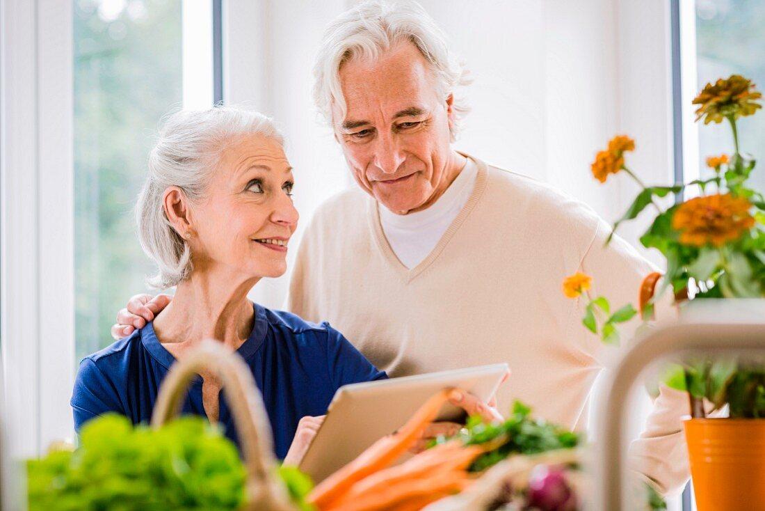 Älteres Paar mit Tablet in der Küche