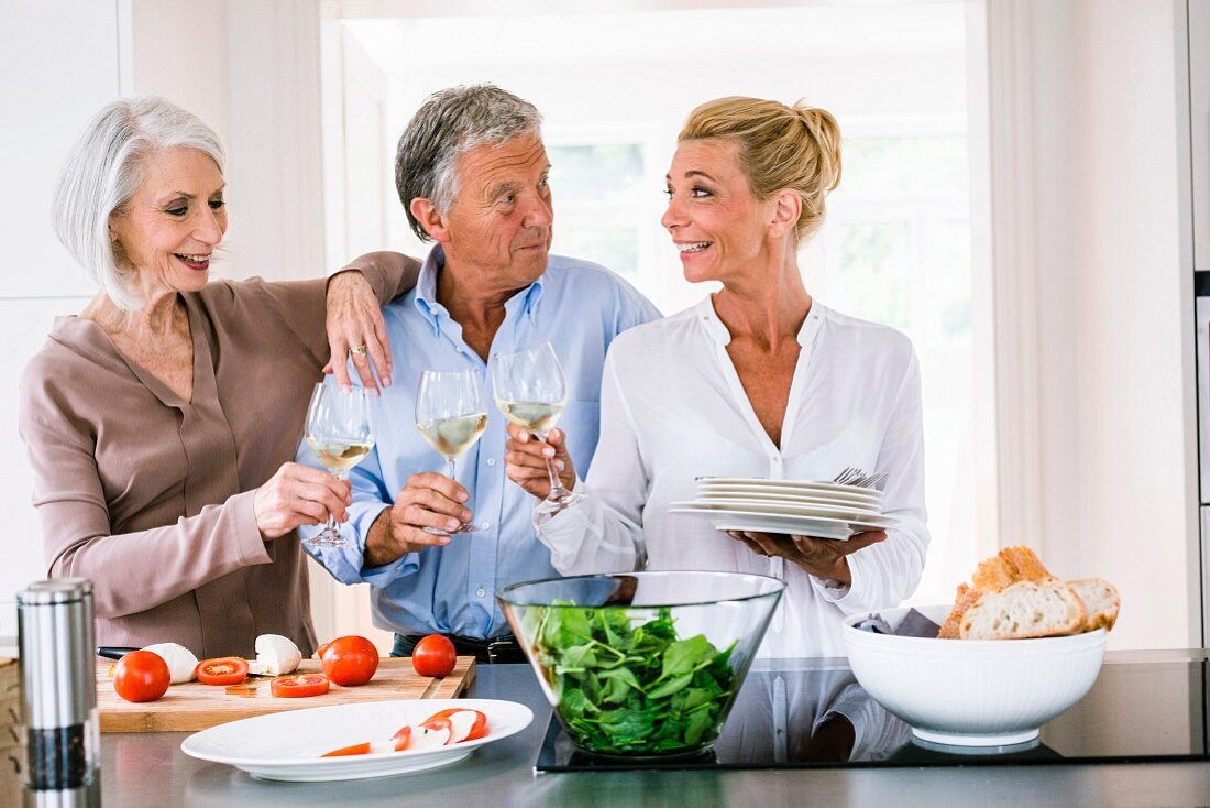 Cooking with friends: three older people toasting with wine in a kitchen