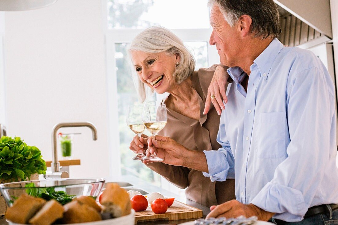 An older couple in a kitchen toasting with glasses of wine